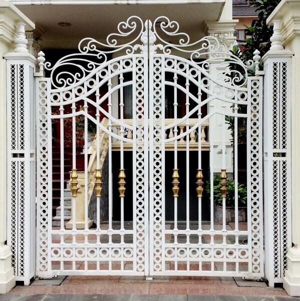 Cổng ngõ 2 cánh sơn trắng với các họa tiết uốn lượn tinh tế