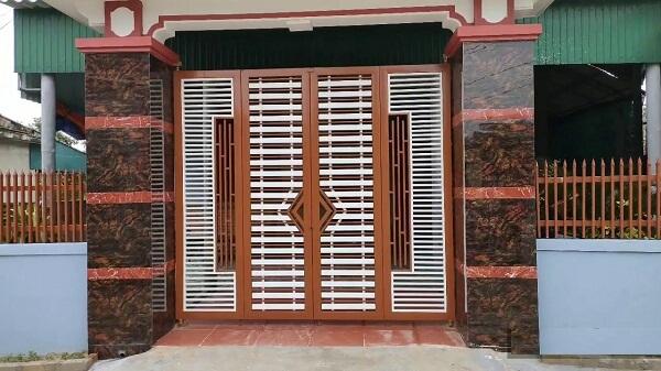 Cửa ngõ 4 cánh khung viền màu gỗ và thanh sắt trắng cùng các chi tiết sắp xếp ngang dọc hòa hợp