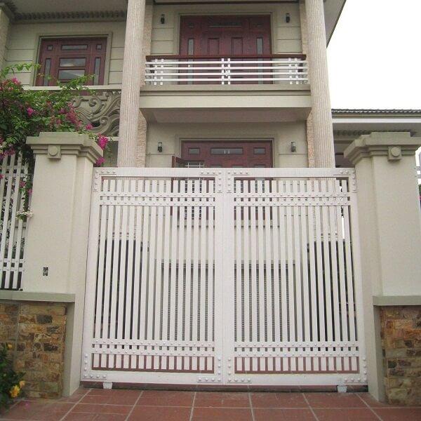 Cửa cổng 2 cánh trắng với các song cửa thoáng đãng gọn gàng