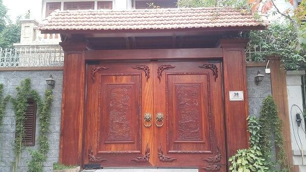 Cửa cổng bằng gỗ kín sang trọng và rất an toàn với nắm tay mở nắm cửa hình sư tử mạnh mẽ